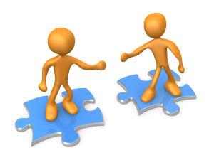 Clipart Illustration of Two Orange People On Blue Puzzle Pieces,